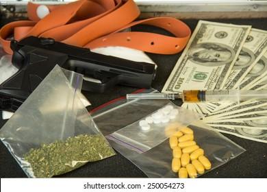 Money, gun and drugs closeup
