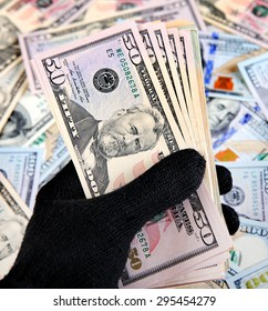 Money in the Hand in the Black Glove on American Dollars Background