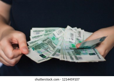 Money in hand. A person recounts money - Russian rubles.