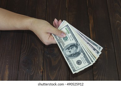 Money in the hand. Woman's hand holds out the money.Pocket money .Bribe.