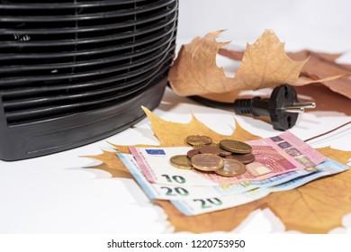 Money for heating bills with black heater on white background. Autumn season.