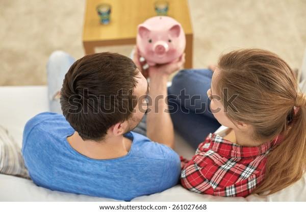お金、家、金、お金、関係のコンセプト – ソファに座っている豚の銀行との接写