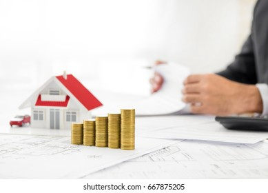 Money and house model on blueprint paper at the table with blurred businessman in background - real estate and property financial concept