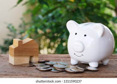 Money for housing. Wooden house model, piggy bank and pile of coins with greenery background. Copy space.