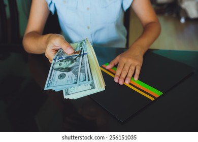 Money in human hands, women giving a lot of 100 dollars, with business folders , on a black background