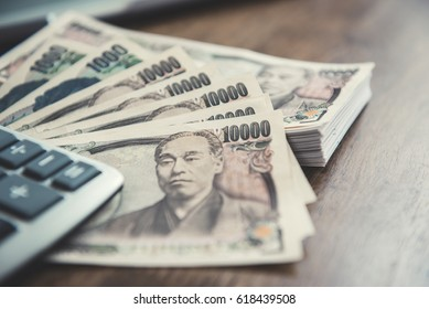 Money, Japanese yen banknotes, on wood table - selective focus