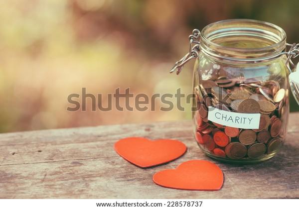 Geldschar voller Münzen für Wohltätigkeitsspenden und ein paar Herzformen