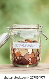 Money jar full of coins with the word crowdfunding on it.