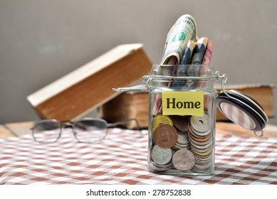 money in a jar and a miniature house on a table