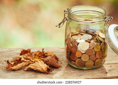 Money in a jar on a table next to some fallen leaves.