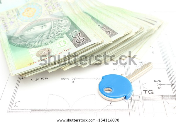 Money with key lying on construction drawing of house