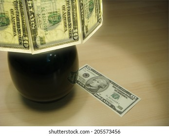 Money Lamp With Light Glowing Through A Shade Of United States Ten Dollar Notes. Shining the light of wealth onto any project. Here a single ten dollar note has fallen from the canopy.