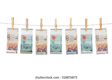 Money laundering concept with Ringgit Malaysia notes on clothesline in plain isolated white background.