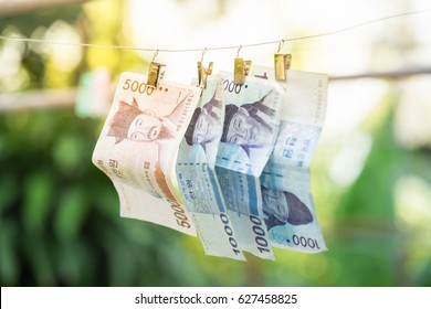 Money Laundering, Currency, Clothesline. Banknotes hanging on a cord, outdoors