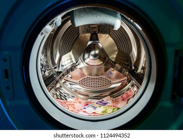Money laundering symbol, chinese yuan banknotes in washing machine with door open