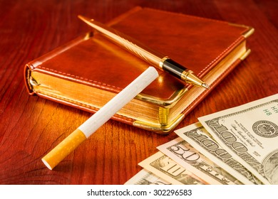 Money with a leather diary and cigarette with golden pen on a mahogany table