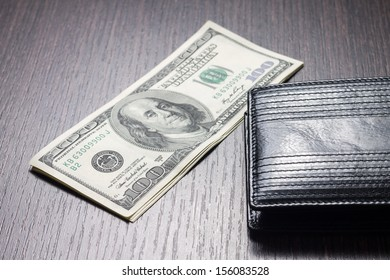 money with leather wallet on table