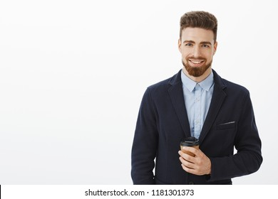 Money likes confidence. Self-assured charismatic and intelligent handsome man with brown hair, beard and blue eyes holding paper cup of coffee smiling happily meeting cute girl after work in cafe