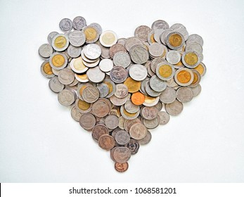 The money for love, care, charity, helpful and donation concept, The isolated image of a lot stack of variety of Thai coins baht placed a heart shape on white texture background