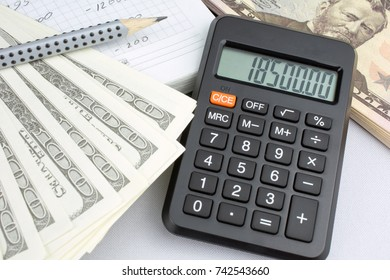 Money made on the stock exchange, dollars, calculator, gray pencil