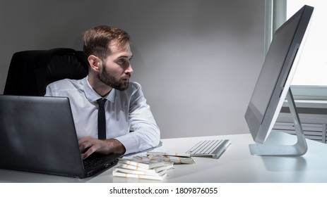 Money manager. Bundles of money on desk of an office worker. Concept - lot of money next to manager. Businessman works with laptop and computer. Manager earns a lot. Dollars near man.