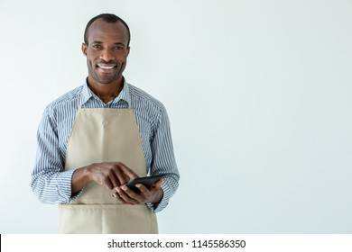 Money matters. Cheerful afro american cafe owner smiling while standing against white background