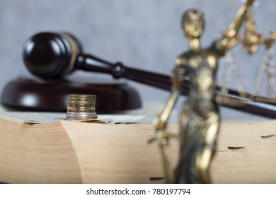 Money on a thick book. Statue Themis and judge's gavel in the background.