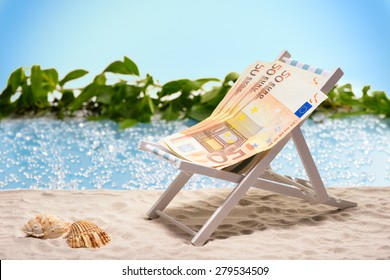 Money on vacation, pack of fifty Euro bills sitting at the beach on a sun lounger in front of a blue lagoon
