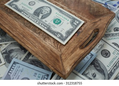 money on a wooden tray, two USD