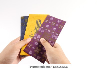 Money packet during Eid Fitr on white. Arabic characters means Happy Eid Mubarak.