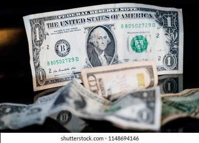 Money. Paper currency. Dollar bill standing on end with black background and money thrown on table top