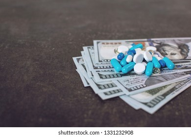 Money and pills. Various medicines and pills on background of USA dollars banknotes. Expensive medicine. Medical insurance. Drug addiction.