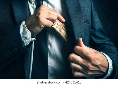 Money in pocket, businessman putting euro banknotes in suit pocket, bribe and corruption concept.