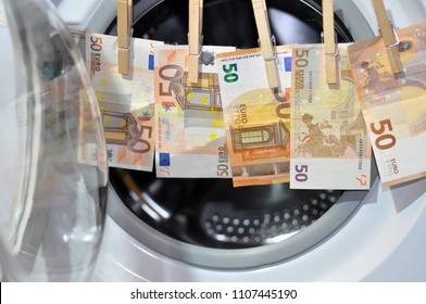Money put to dry with hooks in front of the washing machine. Money laundering symbol, close up