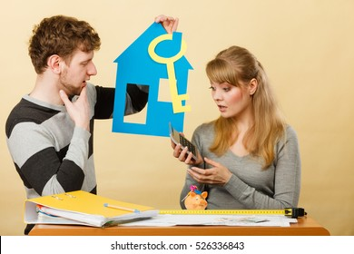 Money and real estate problems. Young worried couple with paper model of house and key. Young marriage calculate expenses.
