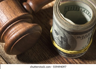 Money roll and judges hammer on wooden table, top view