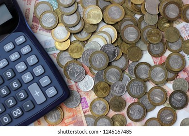 money Russian banknotes of dignity five thousand, one thousand rubles, metal coins 10, 5, 2, 1 ruble background, calculator, concept, selective focus