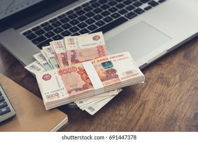Money, Russian Ruble currency, on laptop computer at working table - investment and financial management concepts