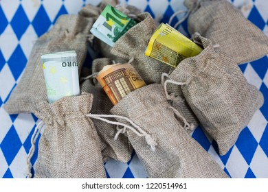 Money sacks on white blue background, bavarian rhombuses, munich, money bag filled with euro