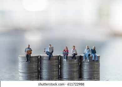 Money, saving and business concept. Group of miniature people figures sitting on top of stack of coins with reading a newspaper and book, waiting and talking.