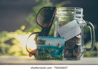 Money saving concept for holidays. A jar of money, sunglasses and a magnet on the fridge as a symbol of putting off on a trip.