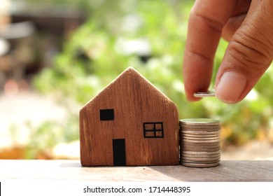 money saving concept image of stack coins and house model ,hand holding coins