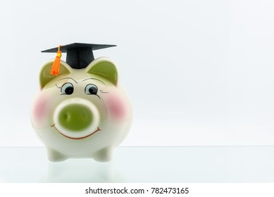 Money saving for education and graduate study program concept : Black graduation cap / hat on a smiley piggy bank, depicts family giving long term investment in child education to secure their future. - Shutterstock ID 782473165