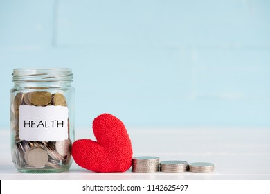 Money saving and health care concept. A jar contains coins with stack of coins and handmade red heart on white and pastel green wooden background.