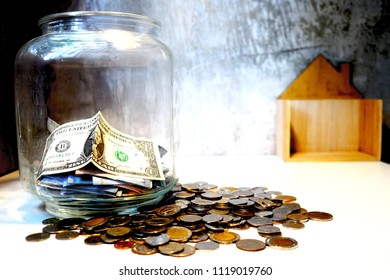 money, saving and investment or family planning concept, over sun flare silhouette tone step of coins stacks with tree growing on top and wooden house model and clock, nature background