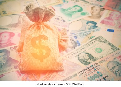Money saving, investment and rich or wealth management concept : Dollar or cash in hemp bags or burlap sacks and coins on yen, yuan bills, depicts prosperous person or billionaire has a lot of money.