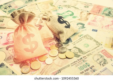 Money saving, investment and rich or wealth management concept : Dollar or cash in hemp bags or burlap sack and coins on yen, yuan notes, depicts prosperous person or millionaire has a lot of treasure