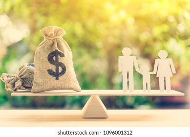 Money saving for kids, family financial wealth management concept : Dollar or cash in hemp bags or burlap sacks and a white paper cut (dad, mom and son) on wood balance scale. Green nature background.