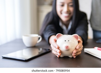 money saving,piggy bank for deposit salary and profit income,hands holding piggy bank for saving money.Individual financial business income,selective focus.