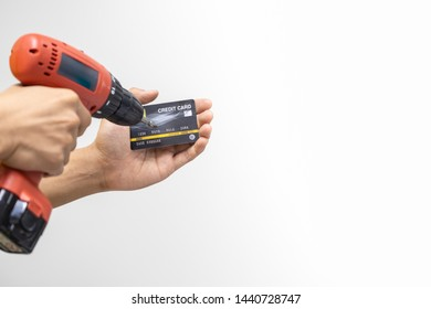 Money and Security Concept. Close up of man hand holding electronic hand drill to destroy credit card with copy space.